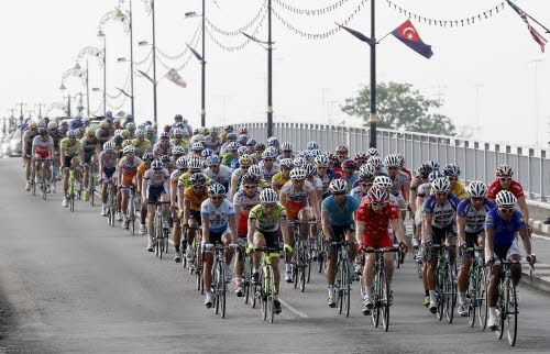 Cyclists pass through a bridge during the fifth stage of Le Tour de Langkawi cycling race in Muar, Malaysia, Friday, March 5, 2010. Malaysia's Anuar Manan of Geumsan Ginseng Asia won the fifth stage with time result 2 hours 23 minutes and 11 seconds. (AP